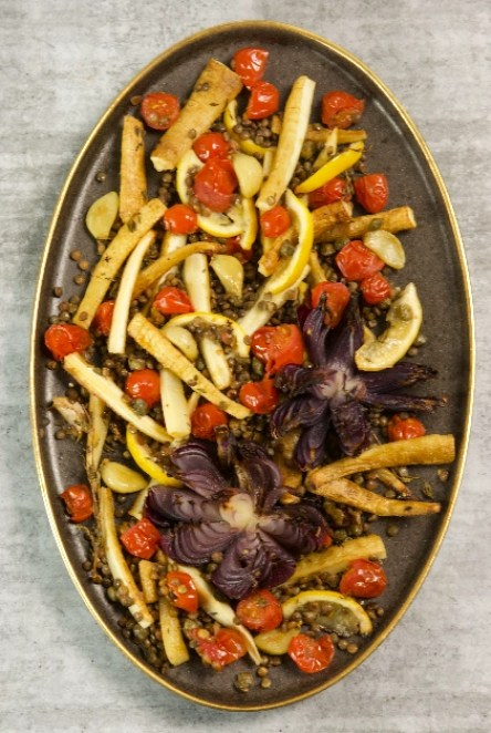 Gilt ended platter with roasted red onion flowers and parsnips, lentils, cherry tomatoes, lemon and garlic cloves