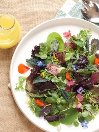 White platter of freshly picked seasonal salad greens with a jug of vinaigrette