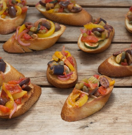 Brown wooden board with crostini and colourful caponata antipasto