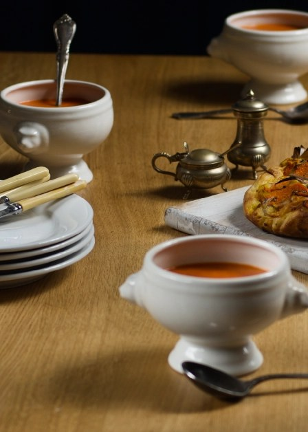 bowls of red pepper soup on a dinner table with butterkin focaccia