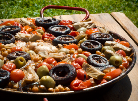 A vegetable paella with mushrooms, tomatoes, artichokes a green olives
