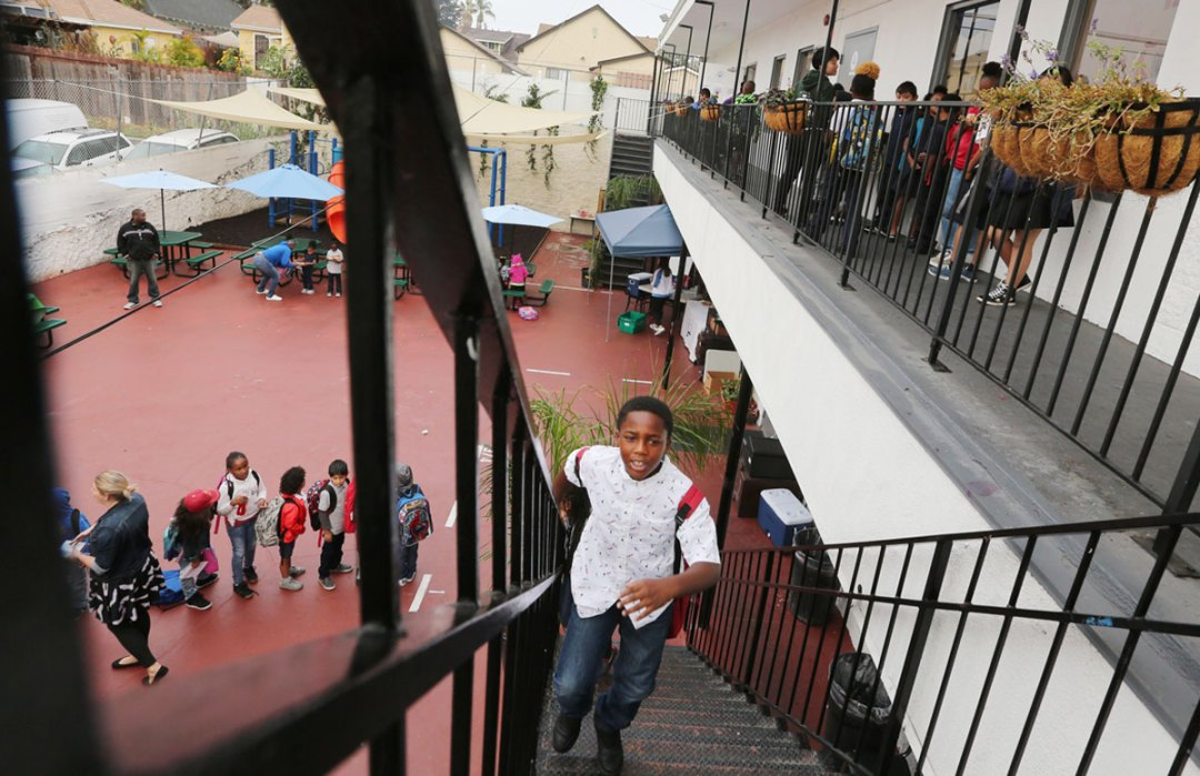 Young student climbing up stairs to get to class at Crete Academy.