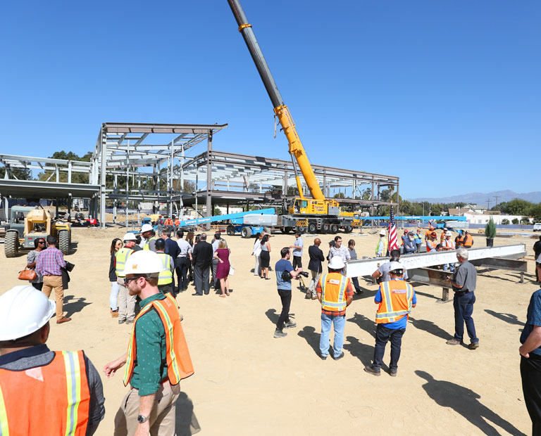 Members of the LAFC and Cal State LA participate in a pole-topping ceremony on the construction site.