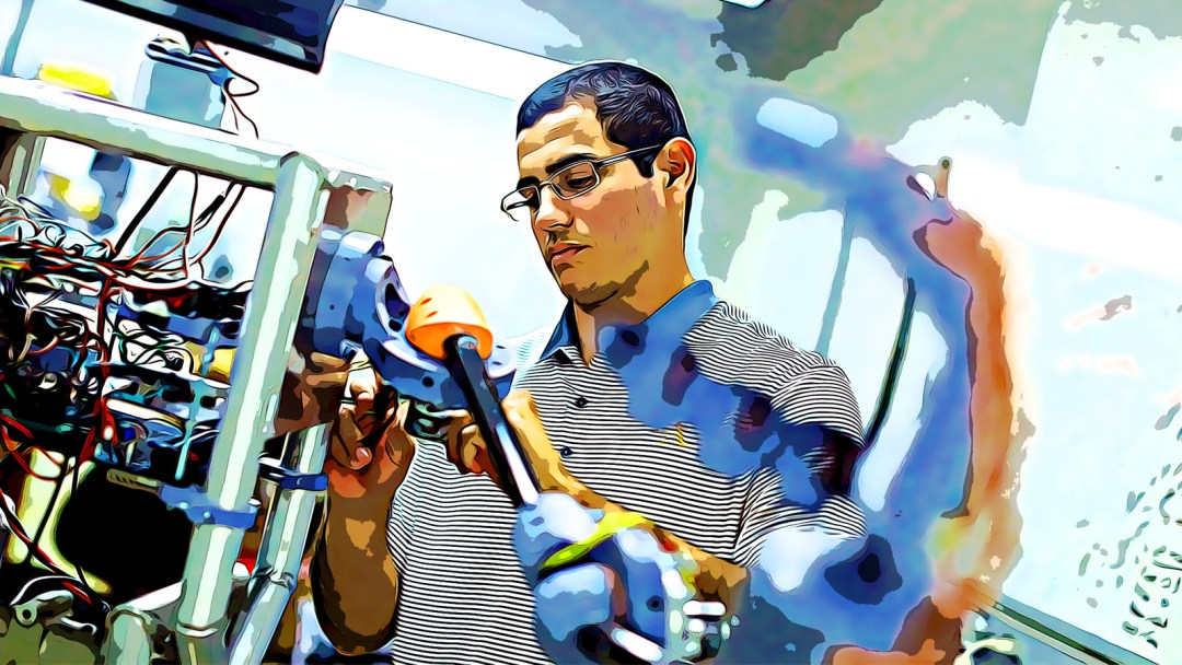 Salvador Rojas working on a piece of technology in a lab.