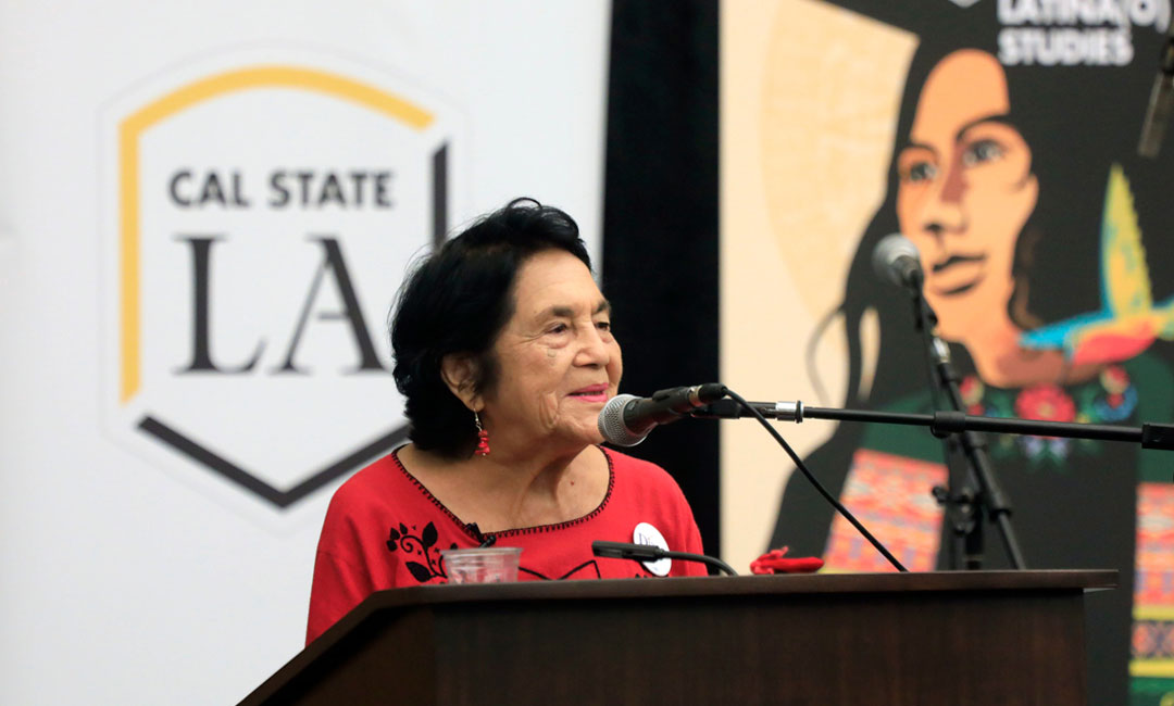 Dolores Huerta speaking in front of a podium at Cal State LA