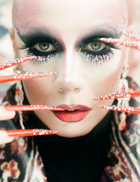 Lorina Rey, a Russian drag queen, showcasing her long red studded nails.