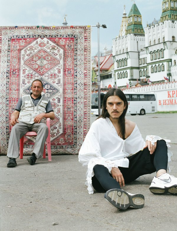 Nikita Kalmykov, a Russian fashion designer, sitting on the ground while an older man sits in a chair in the background.