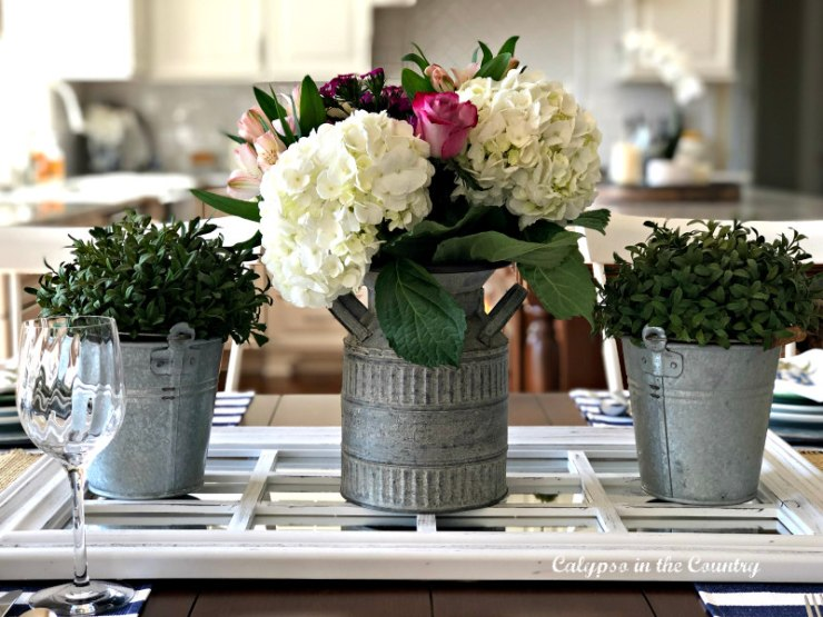table centerpiece with spring flowers in galvanized containers