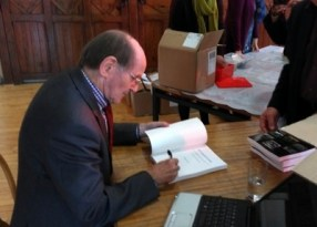 Denley signing his book