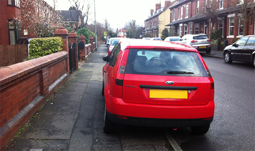 car parked on a pavement obstructing use by pedestrians