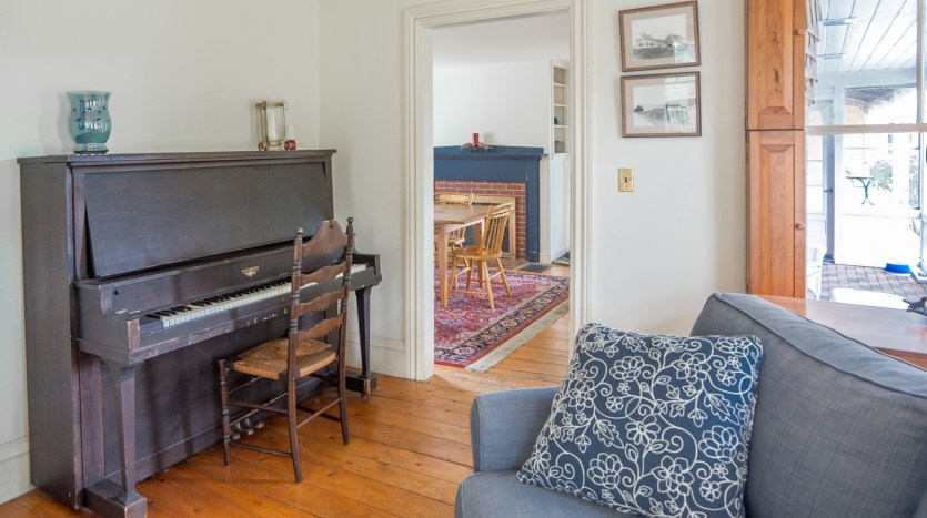 Living room with piano off dining room