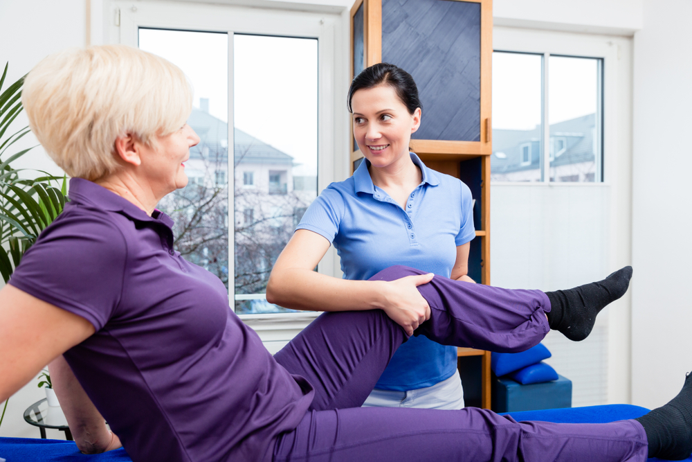 Doctor checking knee joint of senior woman