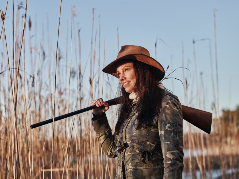 Waterfowl hunting, female hunter carry a shotgun, reeds and blue sky on background - close up and horizon format