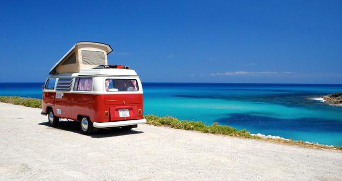 Ein roter Camper parkt mit Blick über das blaue Meer.