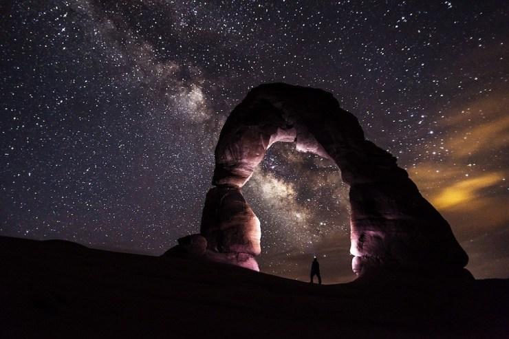 Ein Felsenbogen vor einem Sternenhimmel im Arches Nationalpark.