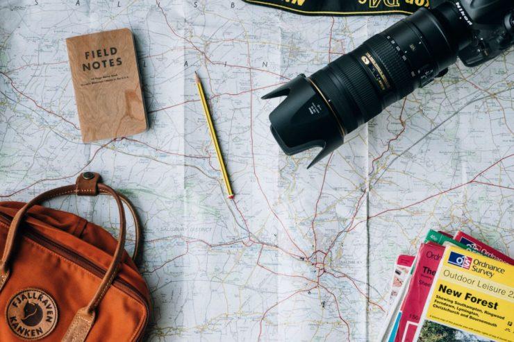 Rucksack, Kamera, Notizheft und Straßenkarten liegen auf einer ausgebreiteten Karte.