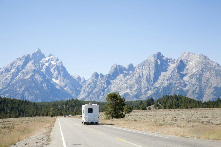 Wohnmobil auf einer Straße vor einem Gebirge.