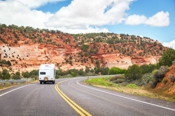Wohnmobil fährt entlang roter Felsen in den USA