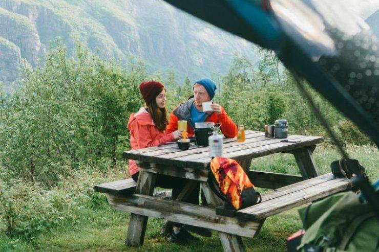Paar sitzt an einem Tisch im Freien. Im Vordergrund ist ein Kofferraum, im Hintergrund sind Berge zu sehen