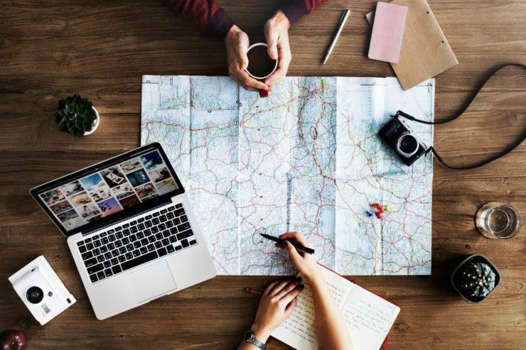 Eine Landkarte, Laptop und Schreibutensilien auf einem Tisch