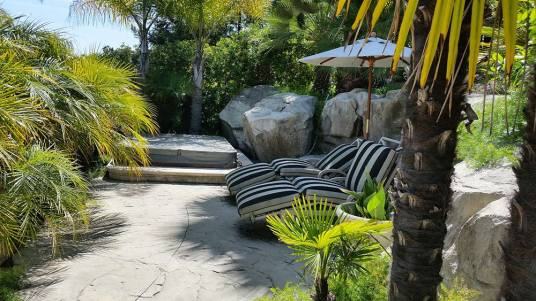 Upper level sitting area backed by boulder walls and surrounded by tropical plantings.