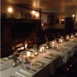 The candlelit historic kitchen set with tables and chairs for a small dinner.