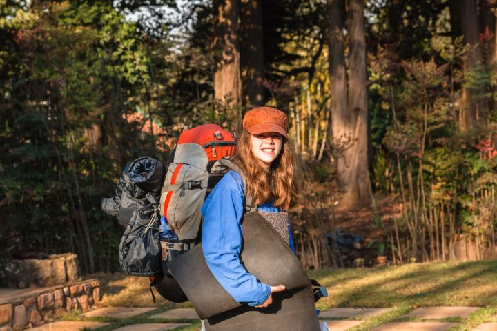 Teenage girl on departure to outdoors with hiking camping backpack