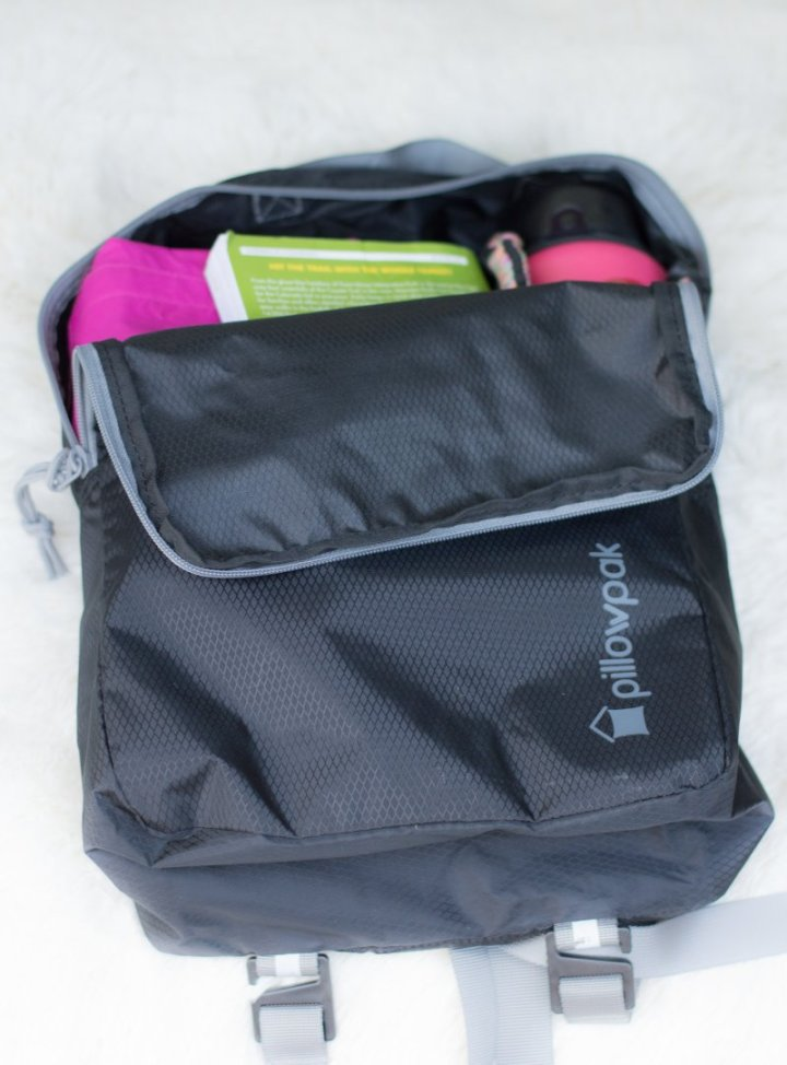 Cubepak unzipped, pink jacket and bottle, green book