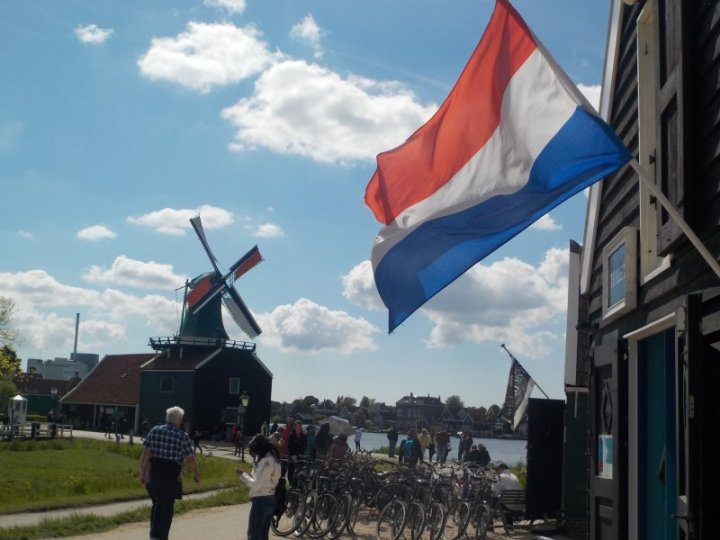 Windmills in Zaanse Schans overlooking the Zaan River, with bicycles under a Dutch Flag. This is the Netherlands!