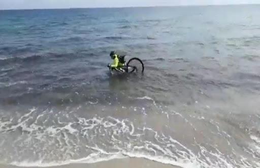 Covid-19, ciclista entra in mare con la sua bici per cercare di evitare il controllo (Video)