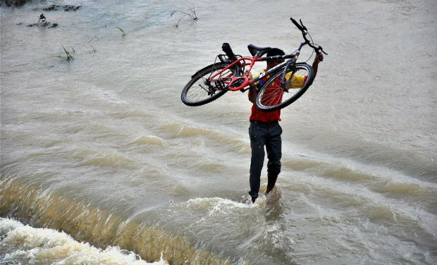 man carrying cycle in floods in pune