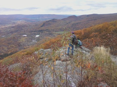 Small group of hikers perched on rocks at top of mountain looking out across Berkshire Mountain fall scenery