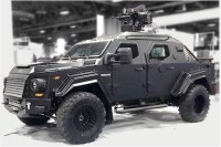 [Photo of a Terradyne Armored Vehicles Gurkha tactical armoured vehicle, with machine gun mounted on top.]