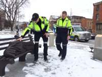 [Photo of Hamilton paramedics amusedly pretending to examining a statue of a sleeping, homeless Jesus on a park bench in winter.]