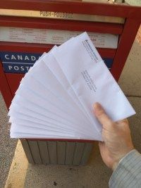 [A photo of Indi's hand holding a dozen letters, in front of a Canada Post mailbox.]