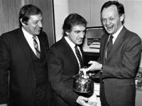 """[Photo taken in 1983 of Roy McMurtry, Roy Romanow, and Jean Chrétien posing with an electric kettle in a recreation of the famous """"Kitchen Accord"""" meeting.]"""