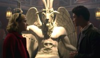 [Screen capture from Chilling Adventures of Sabrina, showing two main characters in the foreground with a large Baphomet statue behind them.]