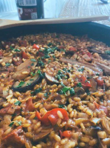 El arroz de verduras, chorizo y setas en sartén