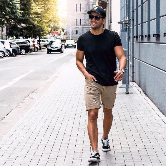 Como Usar Bonés em Looks Masculinos - Bermuda neutra, camiseta preta e boné preto com tênis Vans Pretos