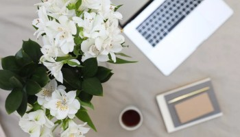 bouquet of lilies placed near laptop and notebook