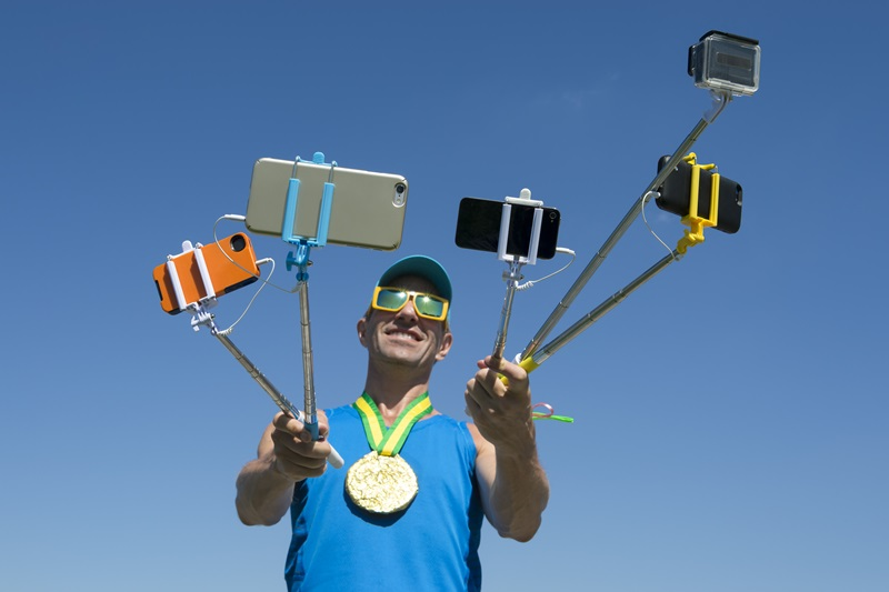 An athlete wearing a gold medal holds several smartphones on 'selfie-sticks'