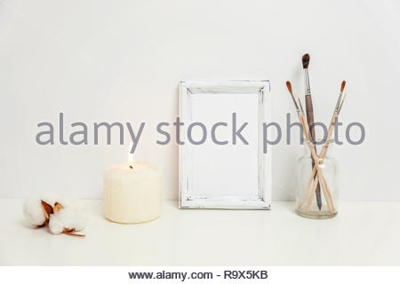 vertical frame mockup with candle brush vase near white wall empty