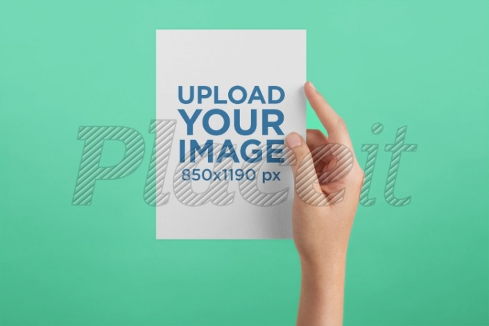 postcard mockup being held against a solid color surface a20557