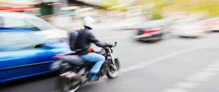 Person Riding a Motorbike on a Busy Road