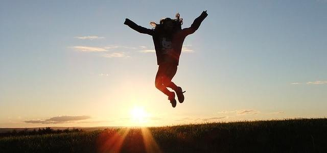 Girl jumping up with sun rising in the background