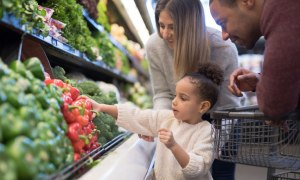 Happy family with child and shopping cart buying food at grocery store
