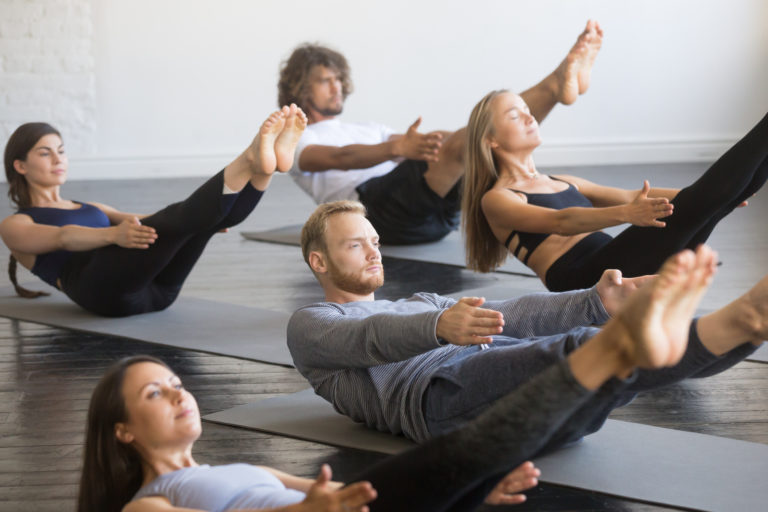 Group of young sporty people practicing yoga lesson, doing Paripurna Navasana exercise, boat pose, working out, indoor close up, studio. Healthy lifestyle concept