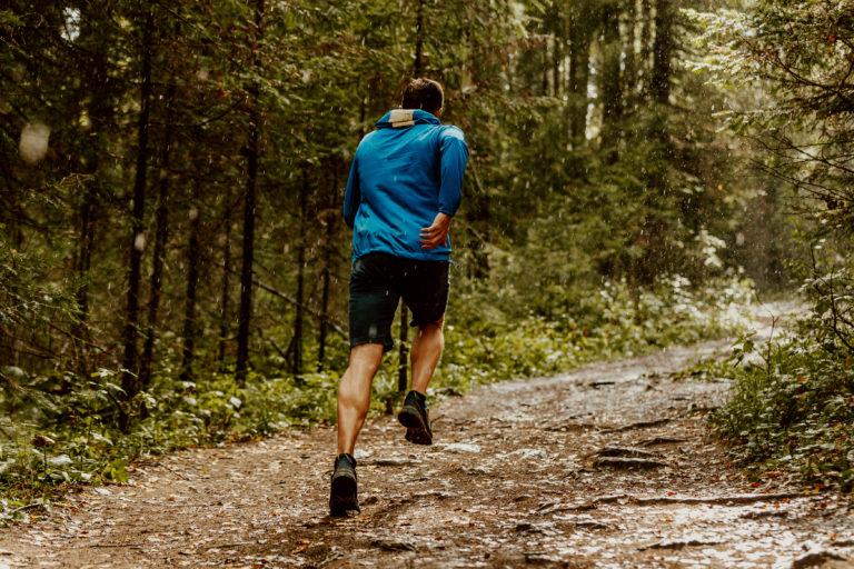 fast running athlete runner forest trail under rain