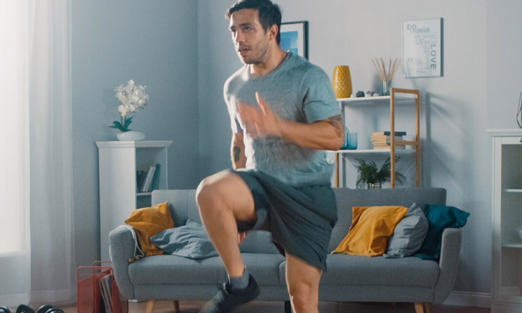 Man in T-shirt and Shorts is Energetically Jogging in Place at Home