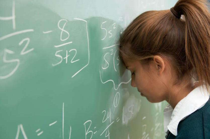 Teenage girl (12-14) resting head against math equation on chalkboard